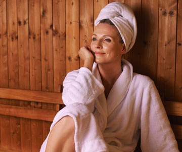 Woman relaxing in a sauna.